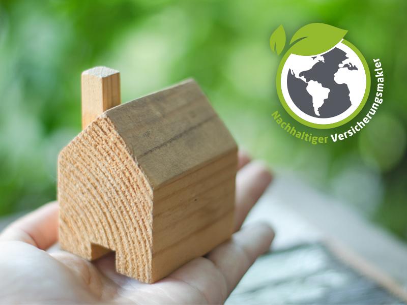 """Kleines Holzhaus in einer Hand, oben rechts Siegel mit Schriftzug """"Nachhaltiger Versicherungsmakler"""". Nachhaltigkeit und Versicherungen von Gentele & Grötsch."""